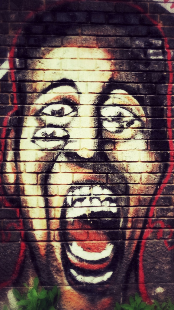 Photo is of a mural of someone screaming.