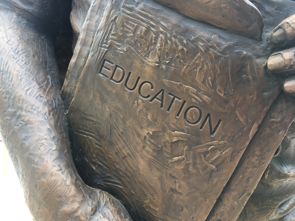 """Photo has a closeup of the part of a statue where it has a sign that says """"Education."""""""