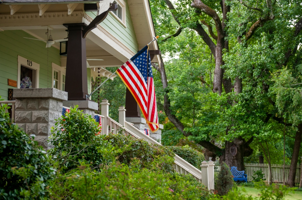 Photo is of an American flag hanging in front of a house.
