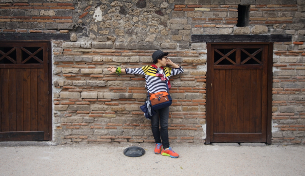Photo is of a person in a striped, multicolored shirt, hat, pants, multicolored shoes, and bag around the shoulder. The person is posing in front of a stone wall with doors on both sides. The person is posing with the right arm stretched out straight along the wall and the left arm bent so that the hand is touching the face.
